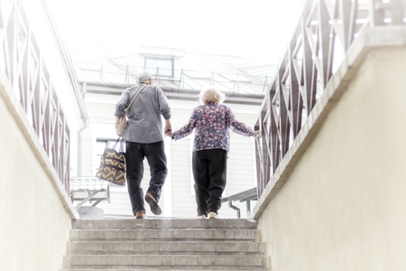 Old Man and Woman Holding Hands and Climbing the Stairs