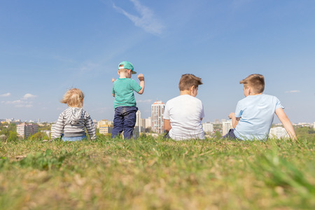 Group of Children Sits in the Park on Background of the Cityscape. Summer Concept