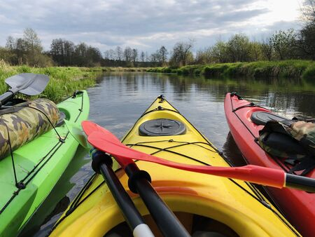 Several Bright Kayaks on the River. Travel and Nature