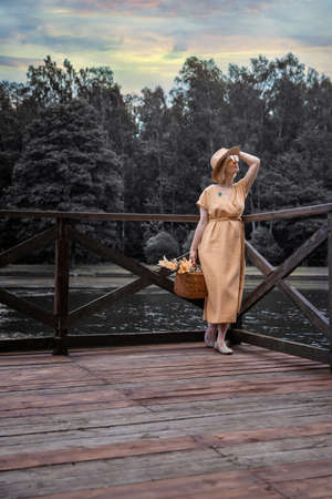 Beautiful Woman in Dress and Hat Walks in the Park Imagens