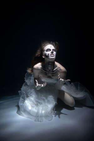 Girl Bride in Dead Man Skeleton Makeup Scares under Water. Halloween concept