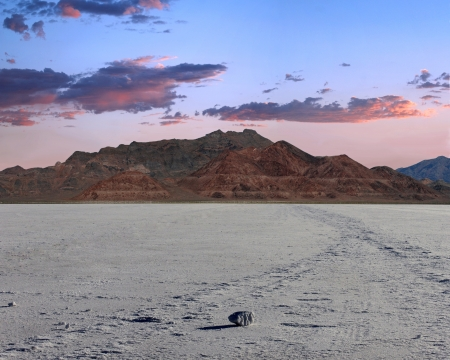 Sunset photo of the bonneville salt  flats. Foreground depicts the salt with a large chunk of salt up front casting a long shadow. mountains in center frame with a beautiful blue to pink sky and clouds.