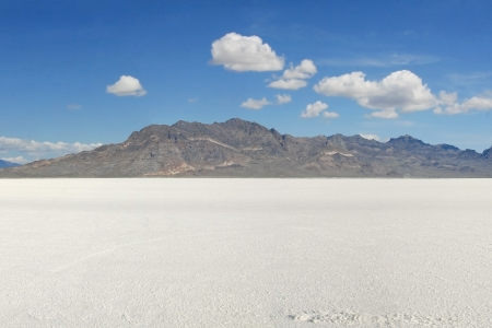 Landscape photo of the Bonneville Salt Flats in early morning. Mountains in photo center and a bright blue sky above with several puffy white clouds. photo