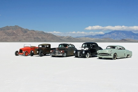 Five hot rods parked on the bonneville salt flats,with mountains in the background.