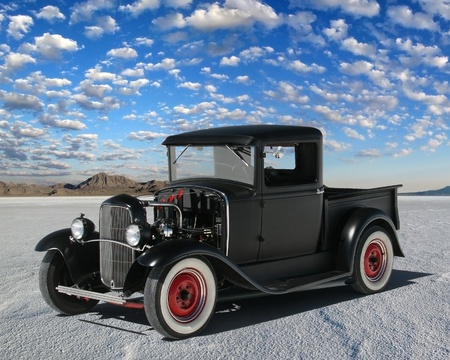 Early 1930s hot rod truck parked on the salt. Truck has red wheels with beauty rings and the body done in black primer.