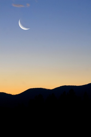 crescent moon: Portrait style photo showing a crescent moon, morning sunrise of blue and orange over the rocky mountains in Montana.