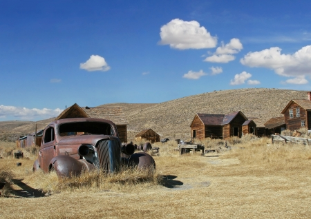Landscape style photo of Bodie historic area with old rusty car on the left and several old bare wood ghost town buildings in frame center,above a blue sky with a few puffy clouds.