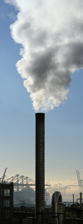 smoke stack: Large smoke stack spewing steam with shipping port cranes in the background and blue sky above.