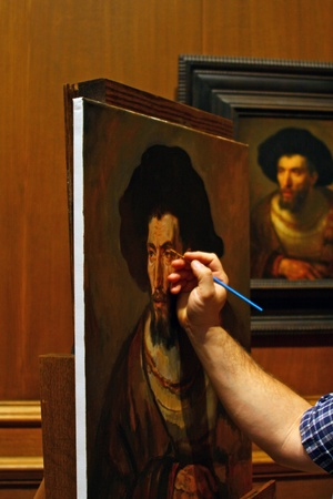 Artists recreation of  Rembrandts The Philosopher  showing the artists hand and brush at work on the painting with the original on the wall in the background. Stock Photo - 12159797