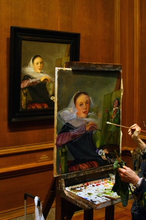 Artists recreation of Judith Lysters self portrait showing the artists hand and brush at work on the painting with the original on the wall in the background. Editorial