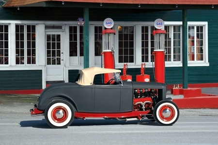octane: 1930s roadster side view  Parked in front of retro service station, red gas pumps with dark green, white trimed building  Stock Photo