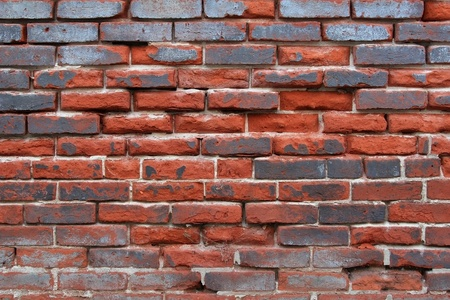 falling apart: Landscape style photo showing an aged brick wall with bricks protruding out giving the appearance that the wall may be falling apart  Stock Photo
