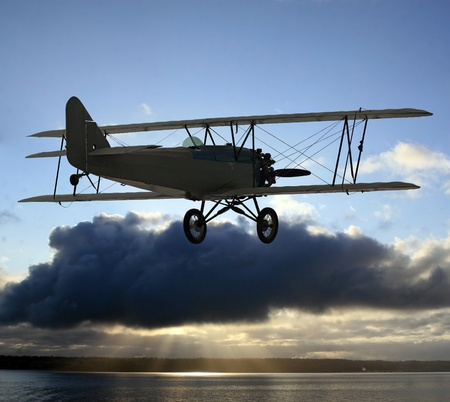 Very early vintage biplane flying above the clouds. Background of blue sky above with clouds in center photo frame covering up the sun and causing light rays to eminate from below onto a large body of water. Stock Photo - 13042518