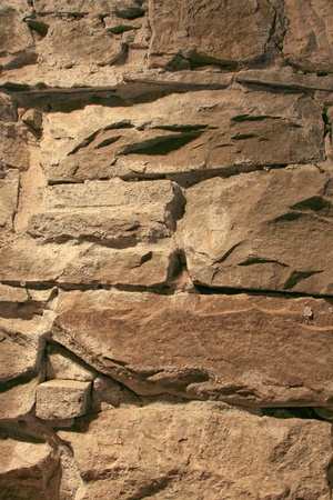 vanished: Rough rock wall used for a foundation late 1800s brick building  Wall is yellowed and much of the mortaring has vanished