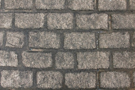 cobble: Man made faux cobble stone sidewalk or pathway closeup,landscape style with a few small pebbles and sand scattered about