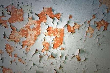 Peeling paint on concrete revealing an orange paint color underneath