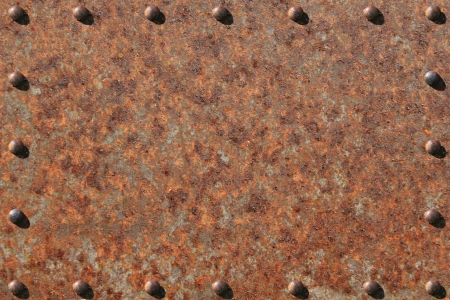 Heavily rusted metal plate, with rusted, riveted edges. photo