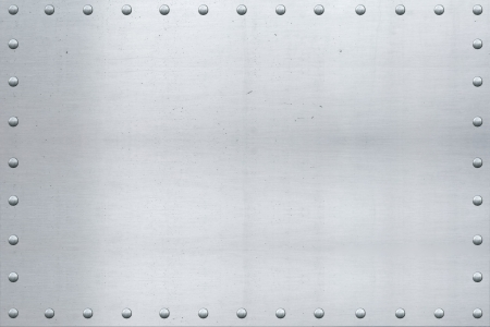 Old aluminum sheet, showing scars and scratches, with riveted edges. photo