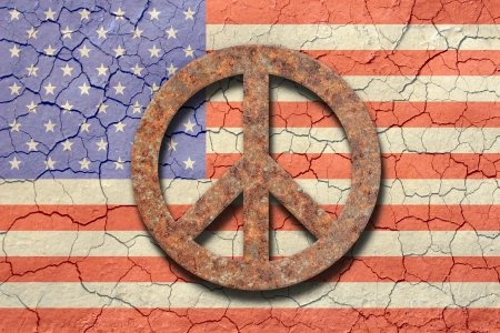 conceptual symbol: American flag background with an arid cracking soil appearance. Up front a rusty peace sign.