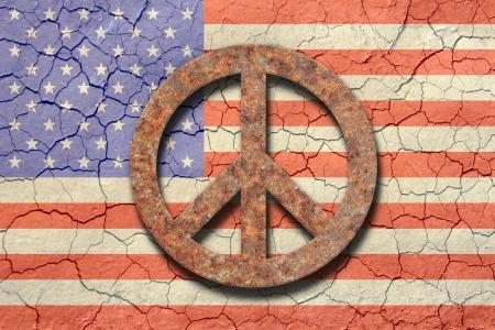 simbolo della pace: Bandiera americana con sfondo un aspetto arido terreno cracking. In avanti un segno di pace arrugginito. Archivio Fotografico