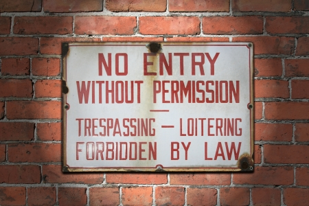 access restricted: Old and aged no entry without permission sign, spotlighted and afixed to brick wall  Stock Photo