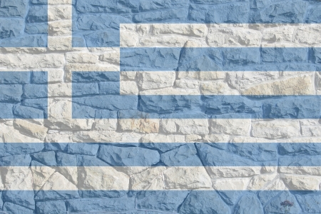 Greek flag atop rock and mortar wall giving an ancient painted on appearance  Stock Photo