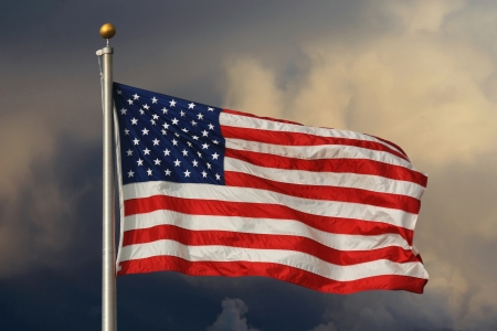 American flag in foreground, waving and brightly lit with ominous clouds in the background.