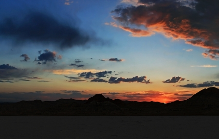 Cloud scattered blue and orange brillant colored sunset over the Bonneville Salt Flats in the foreground with mountains behind. Stock Photo