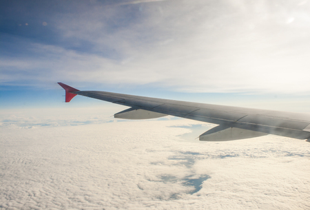 wing airplane high above the clouds Stock Photo