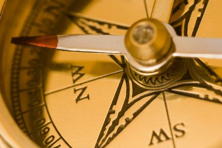 Old style brass compass on white background