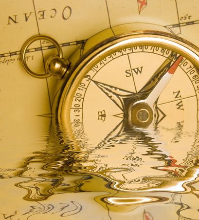 Old style brass compass on antique  map with reflection on water Stock Photo - 723961