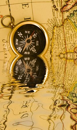 Old Style Brass Compass On Antique Map With Reflection On Water - Antiques us maps with compass