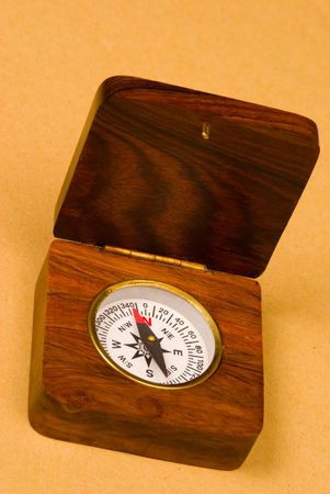 Old style wooden compass on old paper background photo