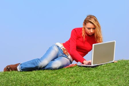 Girl with notebook sitting on grass against sky                                       Stock Photo - 860945