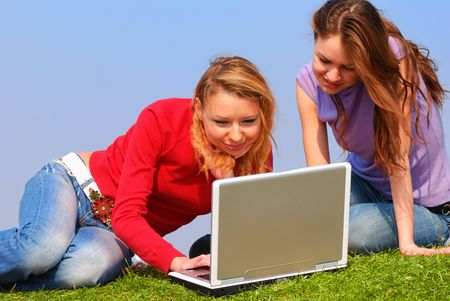 Girls with notebook sitting on grass against sky                                       photo