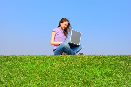 Girl with notebook sitting on grass against sky                                       photo