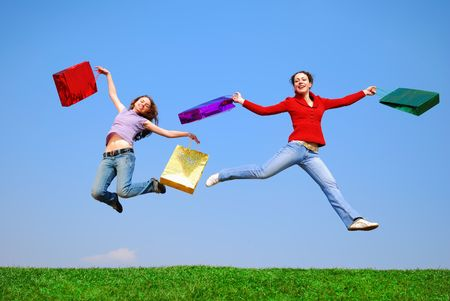 Girls jumping with bags against blue sky photo