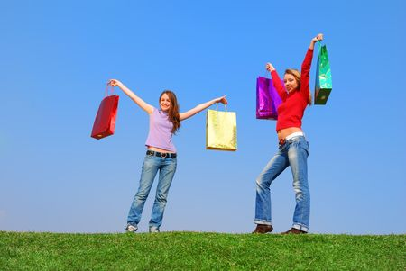 Girls with bags against blue sky photo
