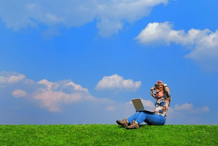 Girl with notebook sitting on grass against sky Stock Photo - 867158