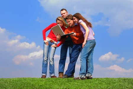 Group of people with notebook sitting on grass against sky Stock Photo - 867159