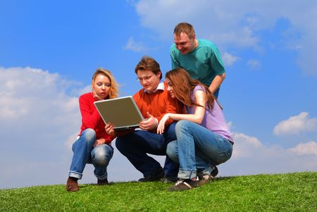 Group of people with notebook sitting on grass against sky                                     Stock Photo - 867160