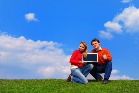 Couple with notebook sitting on grass against sky Stock Photo - 867162
