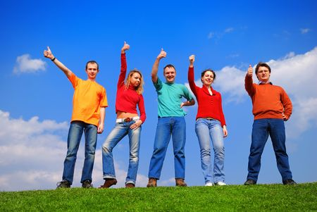 Group of people with thumbs up against blue sky Stock Photo - 867163