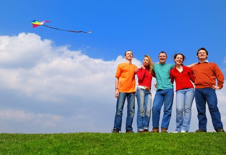 Group of people smiling against blue sky                                     photo