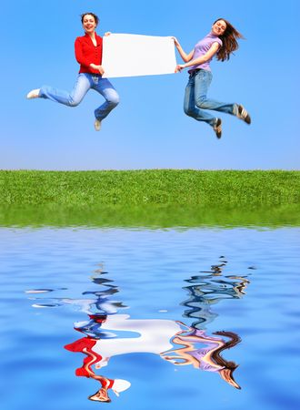 Girls jumping with blank sheet against blue sky with reflection on water Stock Photo