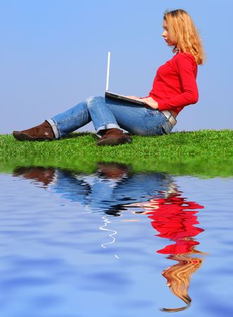 Girl with notebook sitting on grass against sky with reflection on water Stock Photo - 874199