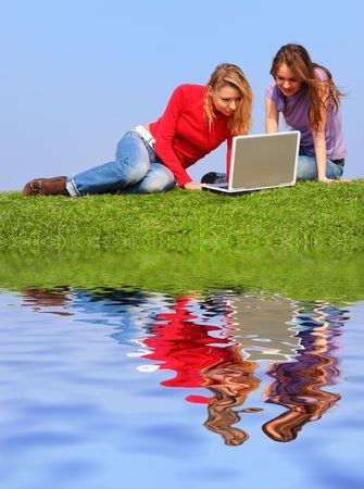 Girls with notebook sitting on grass against sky with reflection on water photo