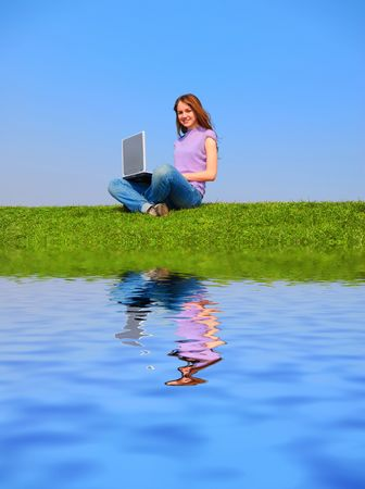 Girl with notebook sitting on grass against sky with reflection on water Stock Photo - 874202