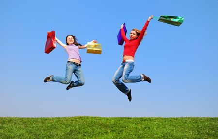 Girls jumping with bags against blue sky Stock Photo - 874204