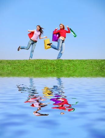 Girls with bags against blue sky with reflection on water photo